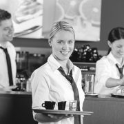 Confident waitress serving coffee with tray